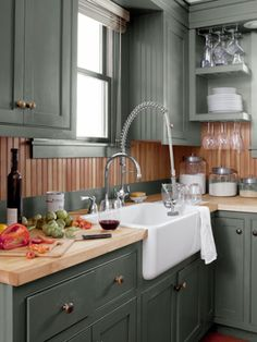 painted  cabinets hunter green and oiled the fir beadboard a golden brown—giving the tight, 75-square-foot spot a jewel box feel. An ivory apron-front sink by Shaws offers a burst of brightness.