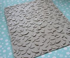 Make your own embossing plate out of old cereal boxes!  Using ModPodge to seal the surface....hmmmm....