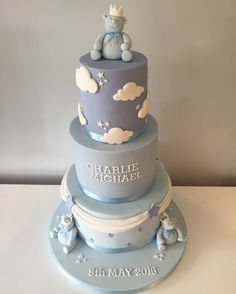 """Beautiful boys christening cake, 3 tiers, 8"""", 6"""" and 4"""", decorated in different shades of blue. Swags on the bottom tier and stars middle tier name and top clouds and stars, finished off with Three cute, fat little teddies."""