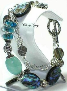 The Shimmer of Water (Le Miroitement de L'eau) A smooth nugget of beautiful aqua chalcedony centers this abalone bracelet. Three borosilicate artist's lampwork beads add depth and presence to the bracelet and pull the colors of the chalcedony and the abalone together. $138.99