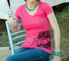 Beautiful, pomegranate pink V-neck burnout tee with cowgirl bareback bronco rider design on hip.