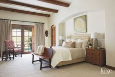 Wood Beam Ceiling Master Bedroom with Neutral Bedding Arched Doorway and Wooden Bench