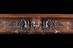 French large wooden chimneypiece with columns and carved head on the frieze.