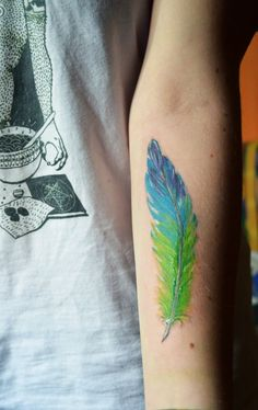 Lime green and blue colored feather done in Sin Perdón Tattoo Studio, Madrid, Spain.