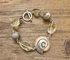 Handcrafted sterling silver wire work boho chic Sterling silver wire work bracelet featuring a stunning .925 hill tribe silver nautilus shell. For this beach inspired beauty, I wire worked rustic looking hill tribe silver beads and lucious lemon quartz nuggets, finishing with a hill tribe silver toggle clasp. #rio jewelry studio
