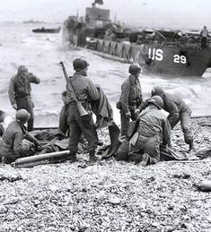 "6th June 1944, Omaha Beach, ""Fox Green"" section. Medics administer a plasma transfusion to a injured survivor of a landing craft that was sunk off the ""Fox Green"" section of Omaha beach."