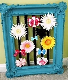 bow holder...vintage frame painted in fun color...ribbon stapled to the back of it...clip the bows on.