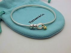TIFFANY 925 Sterling Silver 18k Gold HOOK & EYE BANGLE BRACELET, 6  in. Get the lowest price on TIFFANY 925 Sterling Silver 18k Gold HOOK & EYE BANGLE BRACELET, 6  in and other fabulous designer clothing and accessories! Shop Tradesy now