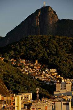 A Rio de Janeiro favela, or slum, at the foot of Christ the Redeemer, illuminated by the sunrise light. www.kimcaptures.com