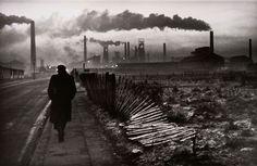Don McCullin: man walks towards series of chimneys on horizon, don mccullin