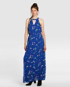 Vestido largo en color azul con estampado floral. Tiene escote halter con detalle de abertura, forro a tono y corte en la cintura.