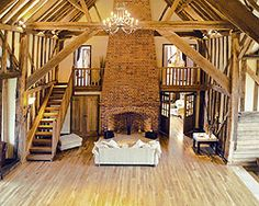 open floor plan. wood beams. chandelier. exposed brick. fireplace. I want to live in a barn.