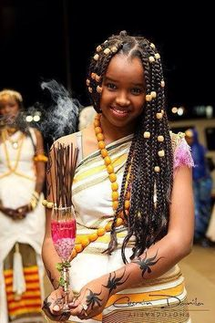 """A Somali girl at a wedding...wears the traditional Somali dress called a guntiino as well as amber across her torso and in her hair. Her arms, adorned with henna, carry incense. Amber has importance in Somali culture and is typically worn by females. As 1 of 3 nations in the world to which frankincense and myrrh grows on plants native to the country...incense in its various forms has great importance in Somali culture..."" (Source: The Real Afrikan Truth)"