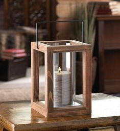 Let the country charm shine! This rustic and stunning candle lamp features a wood frame that holds a tall clear glass cylinder inside. Place the candle of your