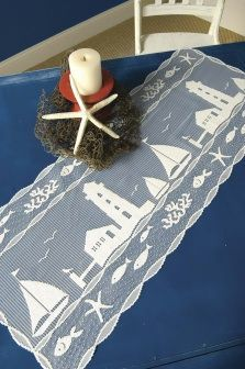 Nautical table runner with lighthouse and sailboat.