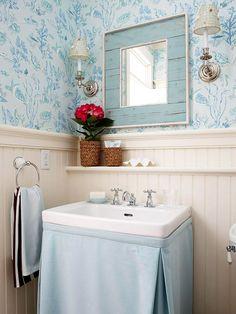Banheiros fora do comum A saia de tecido instalada sob o lavatório com coluna permite diversas combinações e enobrecem este banheiro. Principalmente em conjunto com o lambri de madeira e o papel de parede.