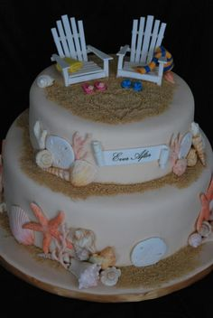 Beach themed bridal shower cake.  Sand is crushed graham crackers, brown sugar and gold disco dust.  All edible. Shells are hand painted white chocolate.  Chairs are sugar paste.  Edible banner too.