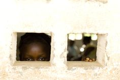 A 13-year-old former sex worker peers out the window of a school in the community of Small Sefadu in Kono District, Eastern Province of Sierra Leone. She attended a meeting of the Small Sefadu Child Welfare Committee, a group responsible for protecting the rights of children within the community.    © UNICEF/Olivier Asselin    http://www.unicef.org