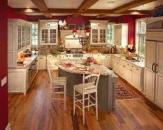 Absolutely love it. The green island ~ red walls ~ white cabinets ~ wood floor ~ French design. Lovely!