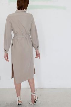 Long, shirt cut dress with buttons hidden under the tab. It has long sleeves, finished in a cuff, creating a delicate puff. Large with a stand-up collar. Tied at the waist with a narrow strap. High cracks on the sides give it a lighter look. The side seams have pockets.