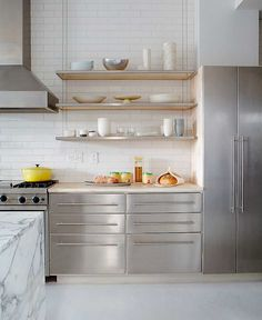 Modern kitchen with stacked stainless steel trimmed suspended shelves over stainless steel cabinets topped with white marble countertops and subway tile backsplash flanked by stainless steel hood situated above high-end stainless steel stove and stainless steel double door refrigerator.