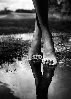She lifts her skirt up to her knees walks through the garden rows with her bare feet laughing..