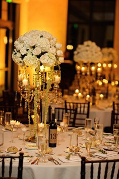 Romantic candles illuminated gold candelabras topped with ivory florals and green amaranthus. #WeddingCenterpiece Photography: Kristen Weaver Photography. Read More: http://www.insideweddings.com/weddings/a-tuscan-themed-jewish-wedding-in-florida-with-natural-details/654/