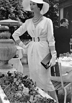 1957 Simone d'Aillencourt in white crépe dress with softly draped bodice cinched by buckled waistband by Nina Ricci,