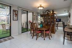 The dining room is open to the living room and is adjacent to the kitchen. It has patio access through the sliding glass doors and a mirrored wall.