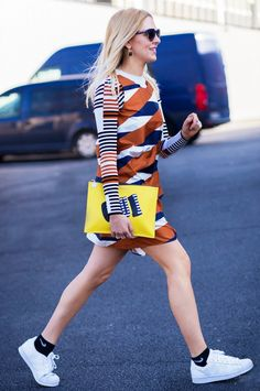 Shea Marie wears a printed pinafore dress with a striped sweater, graphic clutch, statement earrings, and Adidas sneakers