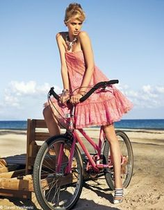 Outdoors in a pink  frock on a  pink bicycle...