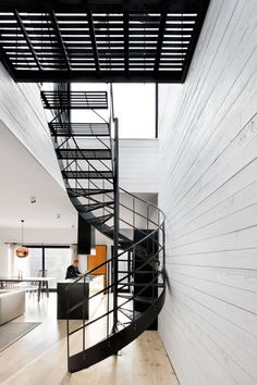 A simple matte black metal spiral staircase with grated steps connects the two main floors of this modern house and lets light easily pass through to keep the space feeling bright and airy.