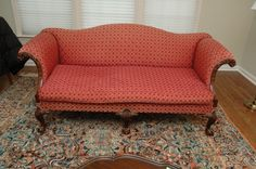 Antique mahogany camel back sofa. Carved floral motif along arms and Chippendale style clawed feet.