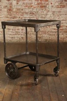 "Item #: TA-4592   Here is a Vintage Industrial Bar Cart that takes your breath away.  The two tiers add functionality to the cast iron table.  It's original and would have been manufactures prior to World War II.  The back caster is 9"" high and the front caster is 5"" high.  This would be great as a Bar Cart, Tea Cart or a Dessert Table."