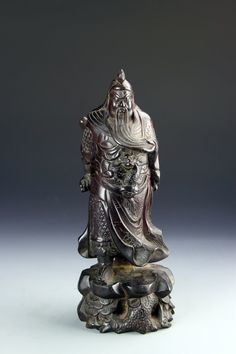 China, zitan Guan Cong statue, with a fierce facial expression and long beard, wearing heavily decorated robes with a dragon in the center. Height 12 in.