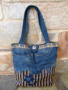 A unique, one of the kind, upsycled jean and fabric tote bag! Pachwork of different fabrics, two front external pockets for your mobile phone, purse,