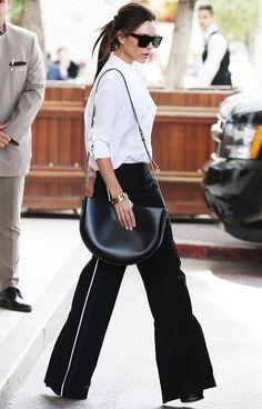 Victoria Beckham usa calça pantalona sporty, camsisa branca e salto.