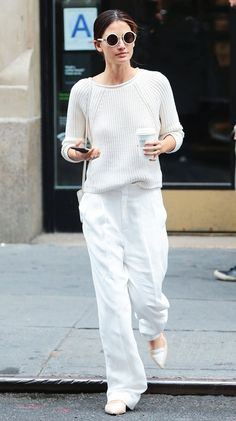 Lily Aldridge wears a white sweater, wide-leg white trousers, neutral flats, and round white sunglasses