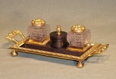 A mid 19th Century bronze and ormolu Pen Tray with mask decoration. (c. 1850 England). A mid 19th Century bronze and ormolu Pentray having cylinder wafer box flanked by cut-glass inkwells above diamond lattice boarder with unusual scroll handles decorated by Comedy/Tragedy theatre masks supported on ball feet.