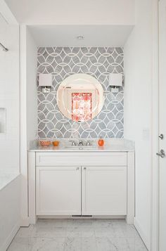 White and gray kid's bathroom boasts a white washstand tucked under a round mirror illuminated by polished nickel wall sconces lining a gray geometric marble lcad wall, Ann Sacks Beau Monde Glass Tiles.