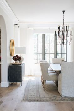 classic dining room design // light wood floors // white dining room chairs