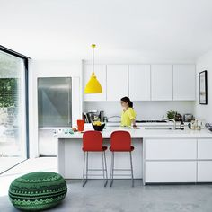 A white modernist kitchen with colorful details.