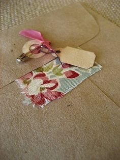 Envelope details - adhere a piece of fabric behind the hole on the flap which allows the envelope to be pinned closed. Add ribbon and mini tag.