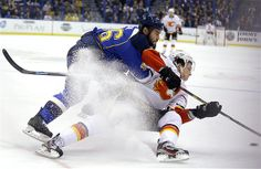 Roman Polak of the St. Louis Blues knocks Joe Colborne of the Calgary Flames off the puck in St. Louis.
