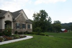 Custom home with stone veneer and board and batten shutters.