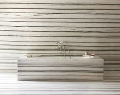A bathroom that is all about the stone byPeter Marino Architect...