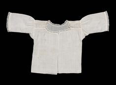 Infant's shirt, 18th century. Fine white linen trimmed on the shoulders with bands of Hollie point with a flowering plant design.