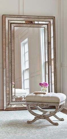 The Duchamps Storage Mirror, set in a wood frame with a multistep, silver painted and distressed finish, rests on the floor and attaches to the wall for stability.