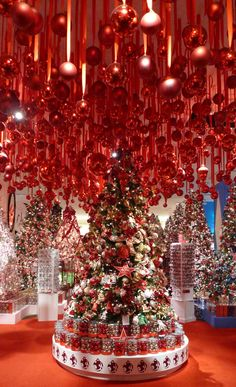 loads of decorated christmas trees love the red ornaments hanging from the ceiling - Hanging Christmas Decorations