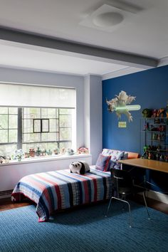A little boy needs lots of space to play and plenty of nooks to keep all those toys. This room keeps the middle of the room open for play space with storage around the perimeter. The window sill and wooden desk provide elevated storage and extra work space. A blue accent wall is complemented by a blue area rug and striped red and blue blanket.